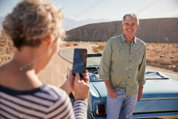 Wife taking shot of her husband on road trip with smartphone