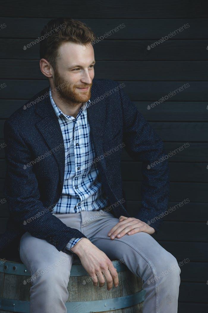 Man in a jacket sitting on a barrel