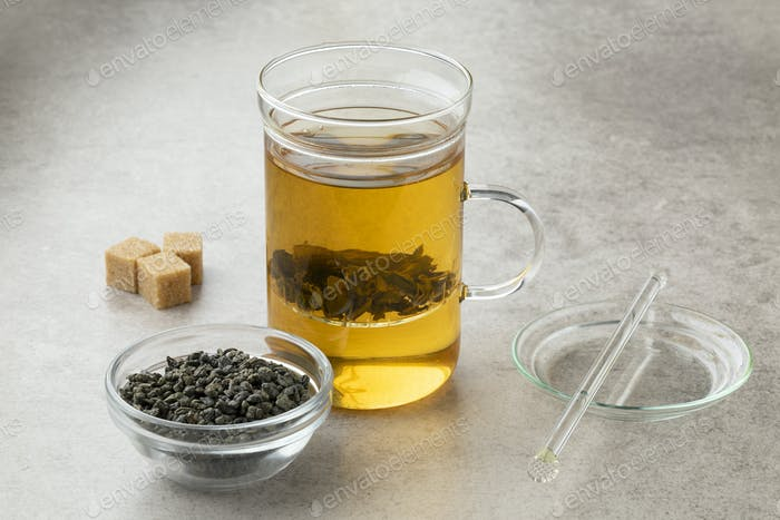 Tea glass with green gunpowder tea and a bowl with dried tea leaves