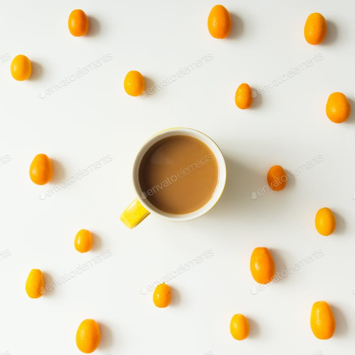 Colourful bright pattern made of kumquat fruit with coffee cup.