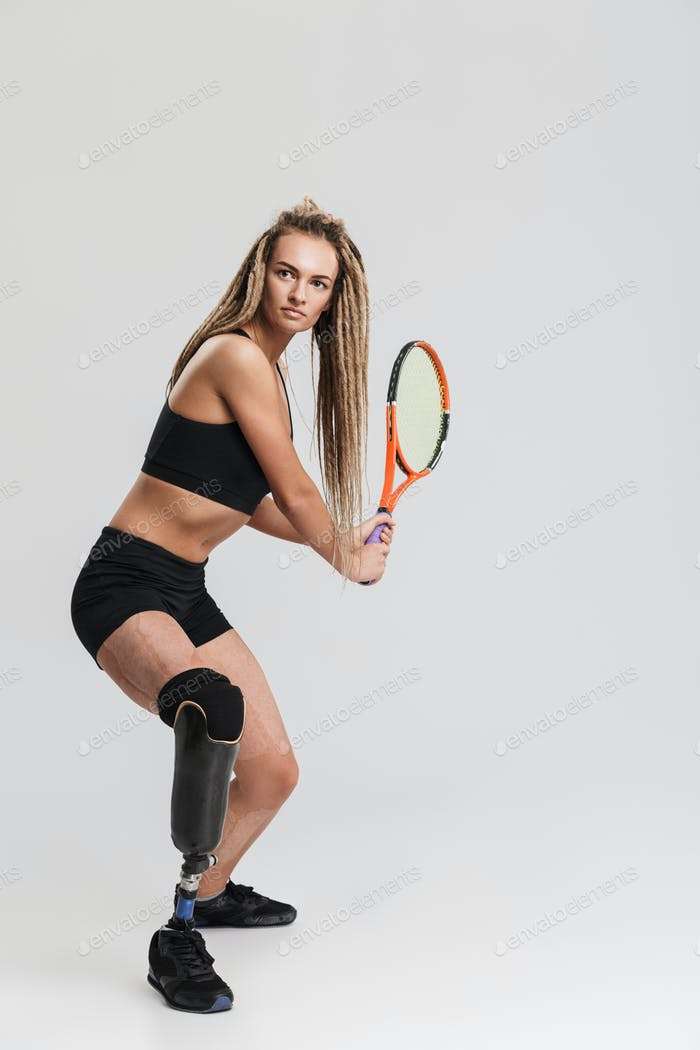 Tennis player standing isolated over grey background