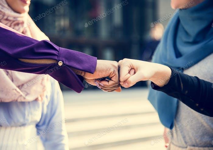 Islamic women friends fist bumps