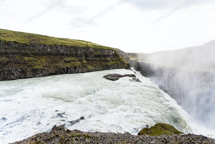 Gullfoss waterfall and water spray over canyon