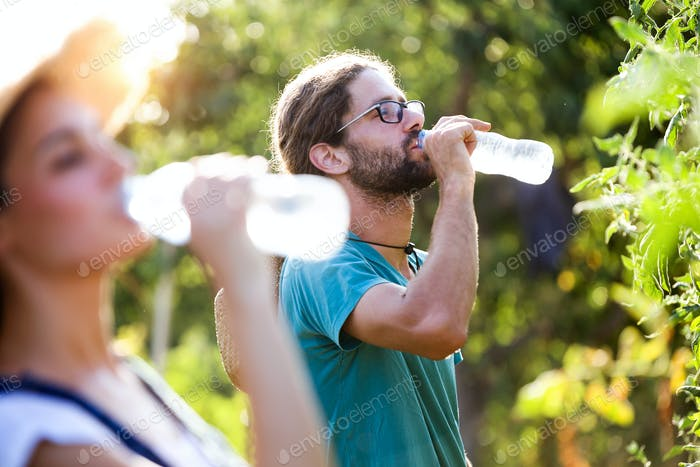 Horticulturist couple having a working break and drinking water