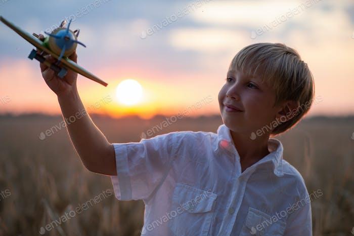 Glückliches Kind spielt mit einem Spielzeugflugzeug in der Natur während des Sommersonnenuntergangs.