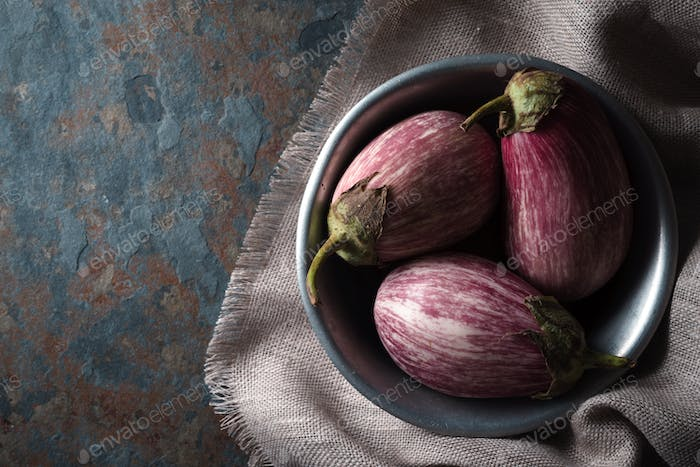 Color eggplants in a tin bowl on a gray napkin