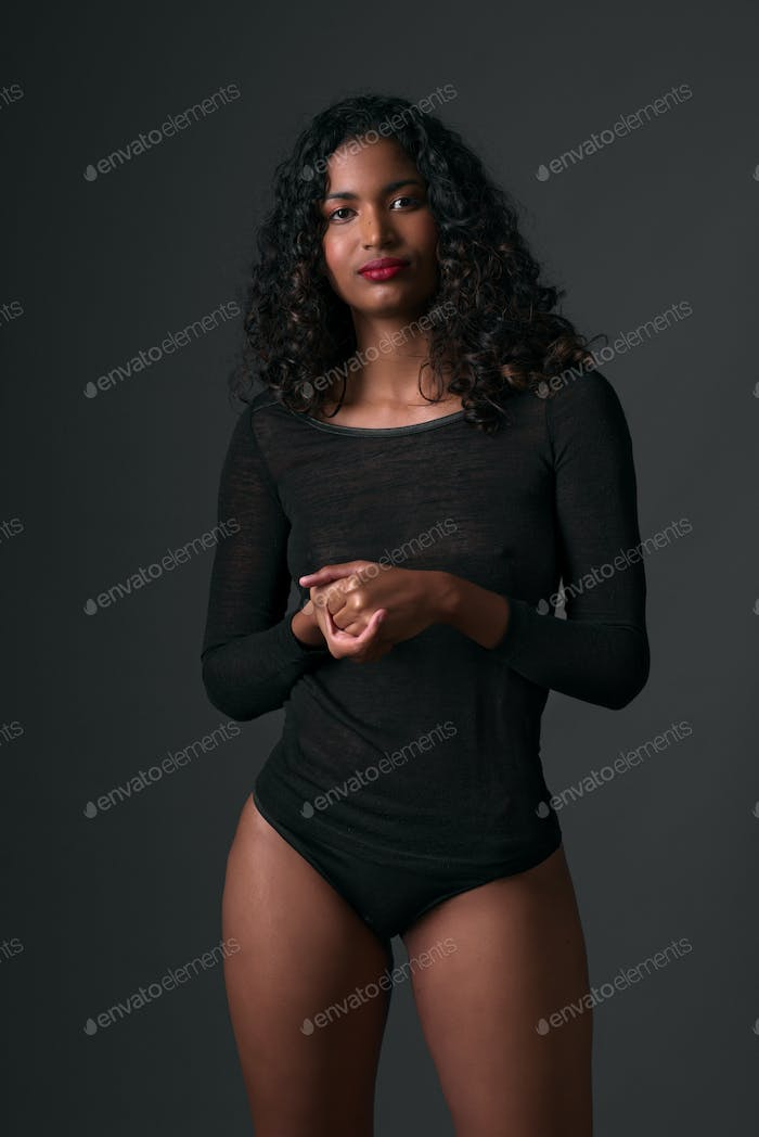 cute young afro asian girl poses in studio on dark background