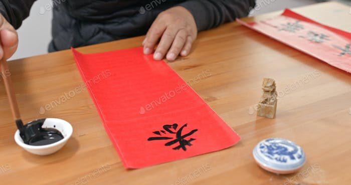 Man write chinese calligraphy for lunar new year, words mean wish you a prosperous Year