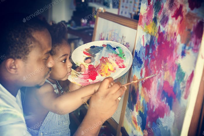 African descent dad teaching his child how to paint