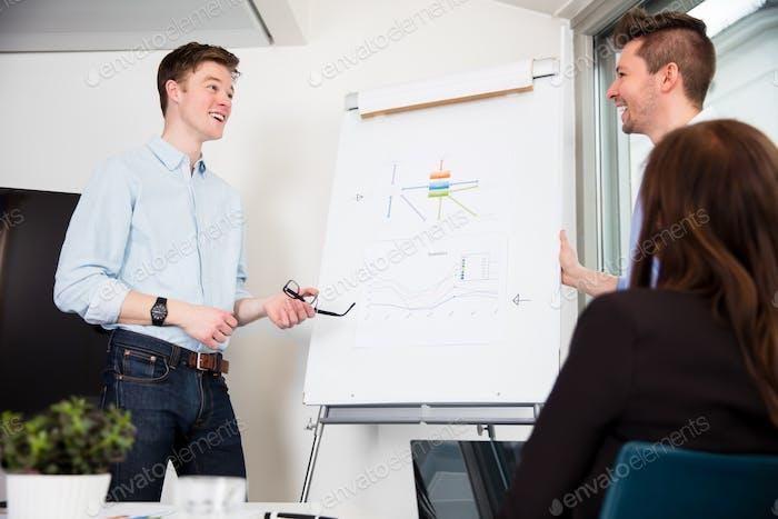 Бизнесмены, стоящие на презентационный совет в офисе