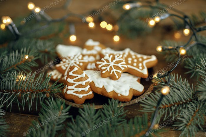 Christmas gingerbread cookies on plate, fir branches, lights on rustic table. Atmospheric winter