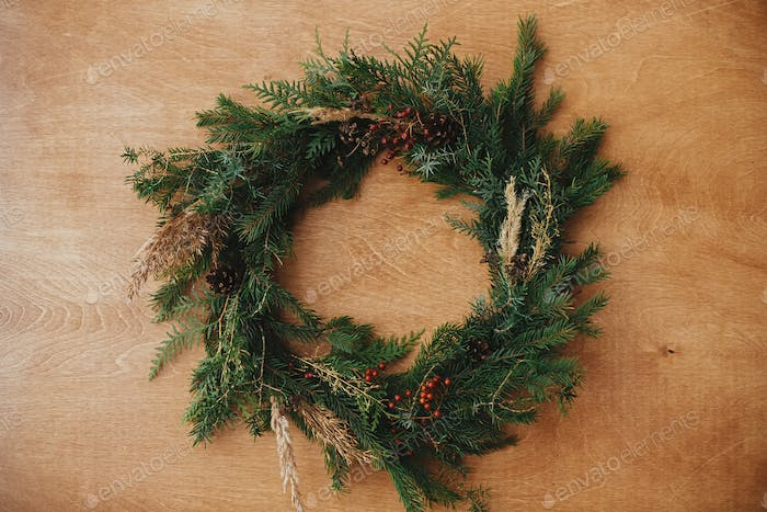 Creative rustic christmas wreath on wooden table, flat lay