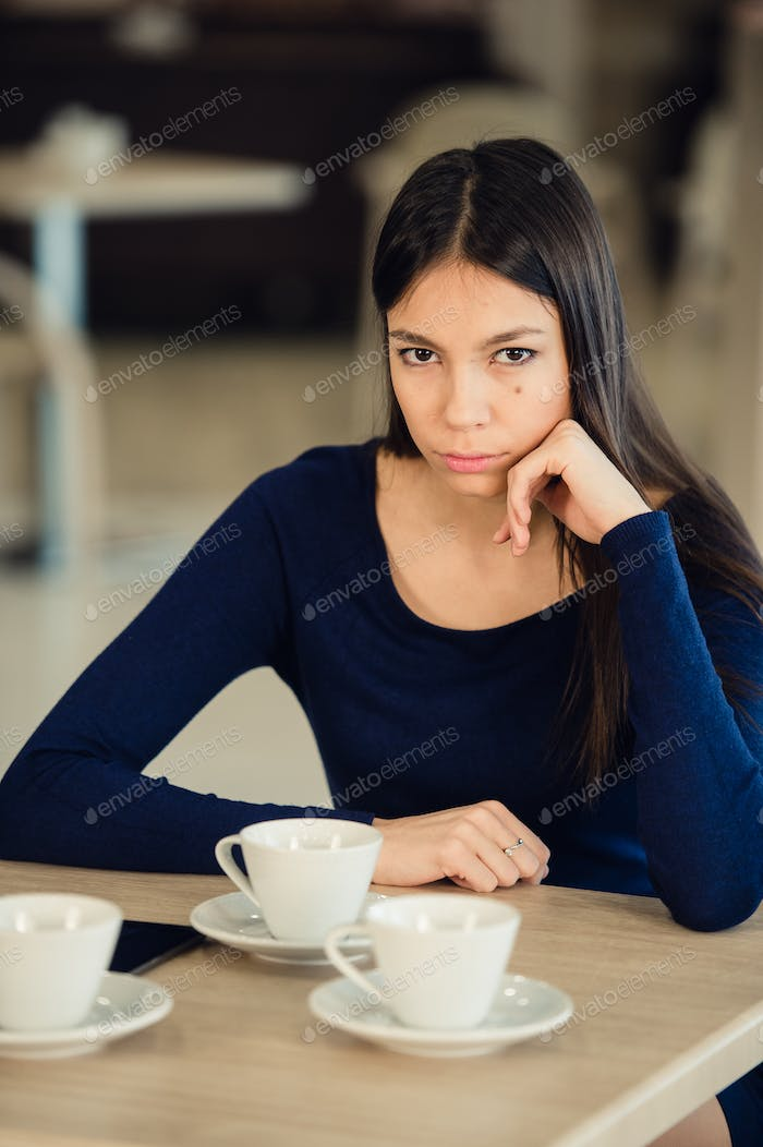 Angry young woman with crossed arms at cafe