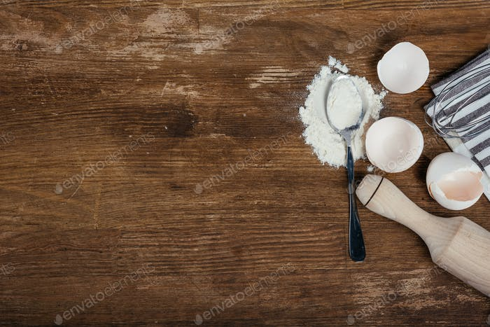 Top view of flour, eggshells, spoon and rolling pin on wooden table