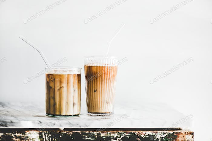 Iced latte coffee in glasses with straws, whate wall background