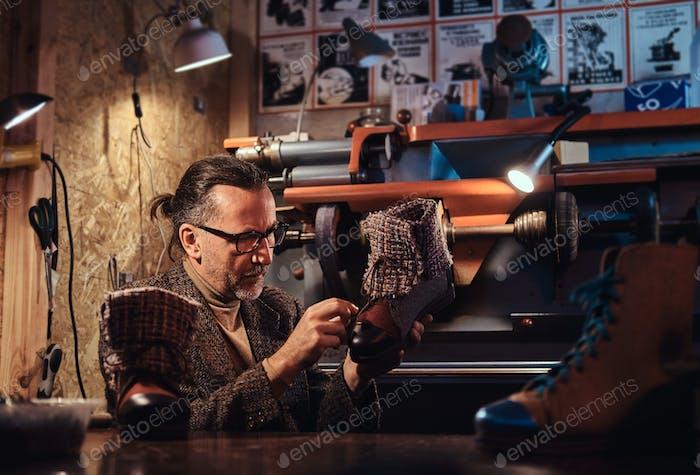Beschäftigter Mann in seiner eigenen Werkstatt