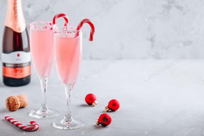 Festliches Weihnachtsgetränk Pfefferminzrinde Mimosa Cocktail mit Champagner oder Prosecco und Zuckerrohr