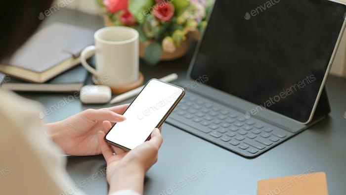 Geschäftsfrau auf der Suche nach wichtigen Informationen mit einem Smartphone für ihr neues Projekt.