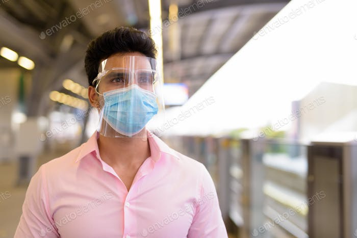 Young Indian businessman with mask and face shield waiting at the sky train station
