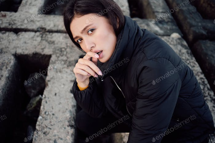 Pensive casual Asian brunette girl in down jacket sadly looking in camera outdoor