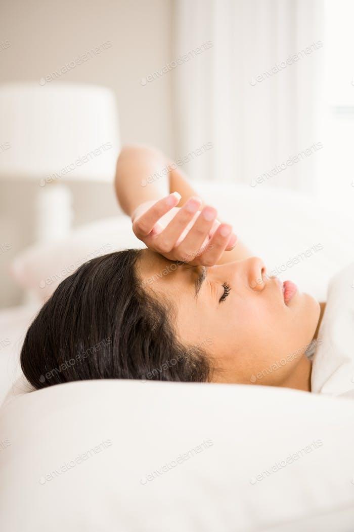 Stirnrunzeln Brünette im Bett mit Hand auf Gesicht