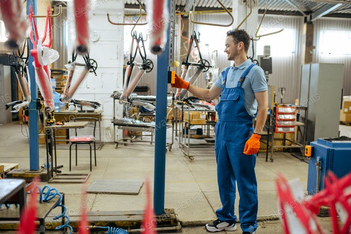 Bicycle factory, worker at bike assembly line