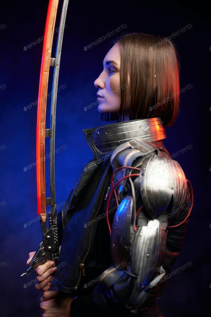 Profil einer kriegerischen und futuristischen Frau, die sich das leuchtende Schwert ansieht