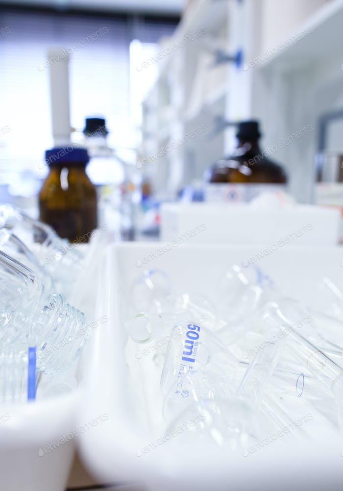 chemistry lab (shallow DOF; focus on the glassware in the foregr