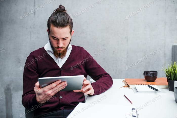 A young businessman with tablet in office, working.