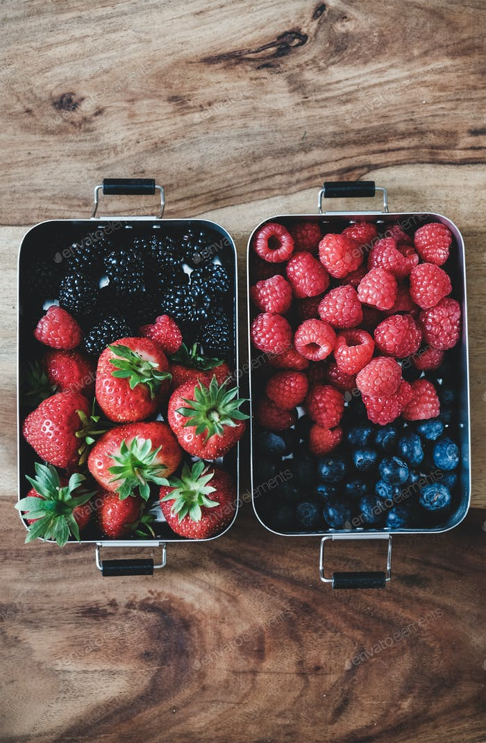 Fresh berries in metal lunchboxes over wooden background, copy space
