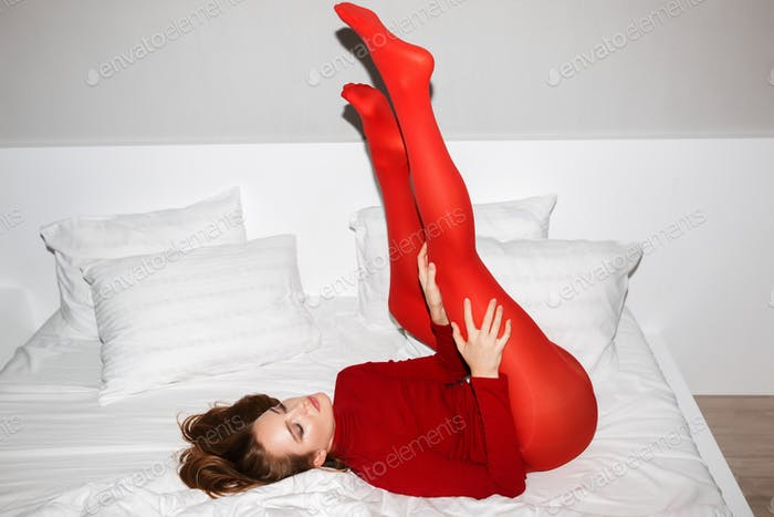 Beautiful lady in red sweater and tights lying with her legs up in white bed dreamily closing eyes