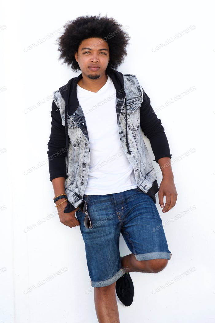 Afro man leaning against white wall