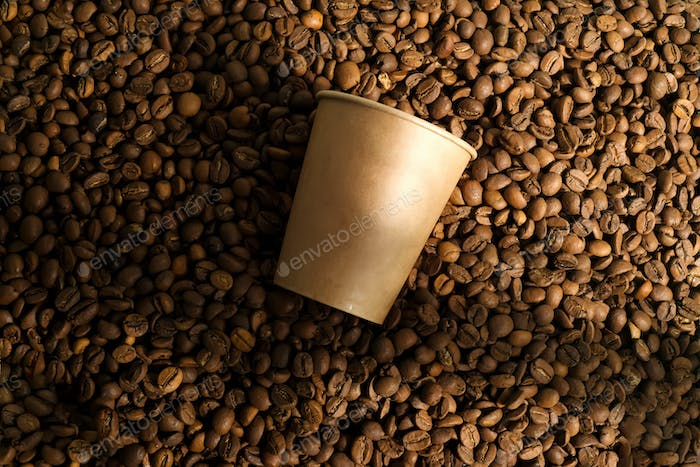Pile of fresh aromatic coffee beans and paper mockup cup