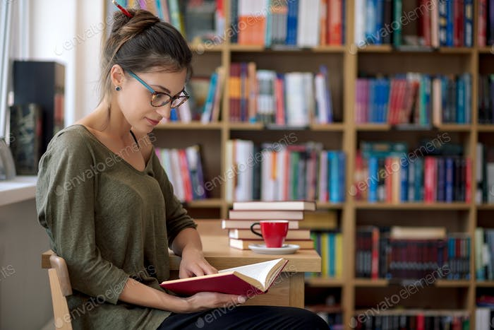 Young beautiful woman reading a book in a library with a cup of
