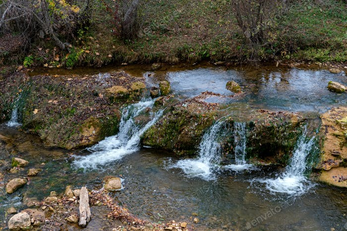 Autumn landscape with mountain dry brook with rapids and lush green