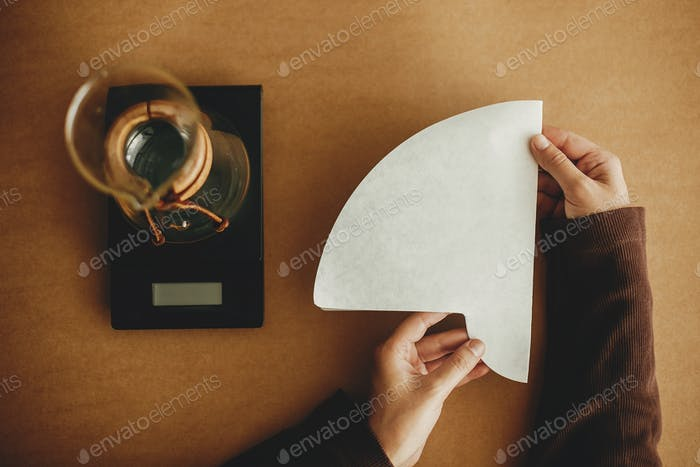 Hands holding paper filter for pour over and glass kettle on scale on brown background