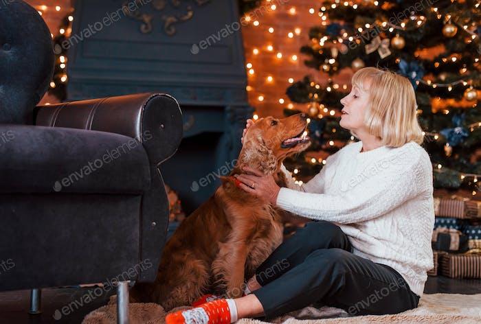 Abuela en el interior con el perro en la habitación decorada de navidad