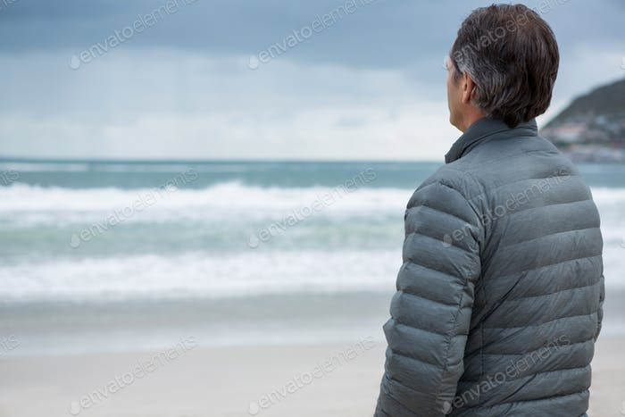 Thoughtful man standing on beach