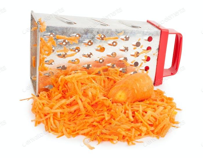 Haufen geriebener Karotten und Reibe