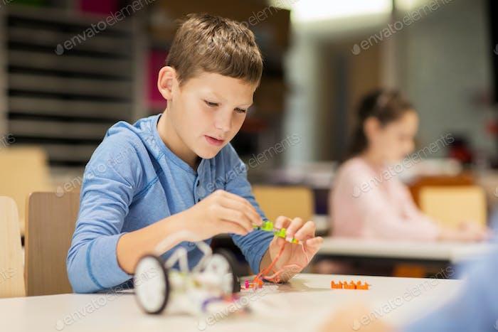 close up of boy building robot at robotics school
