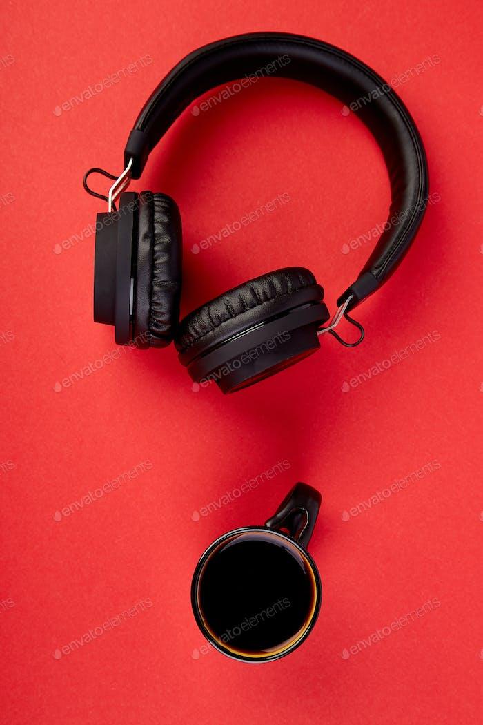 Schwarze Kopfhörer und Tasse Kaffee
