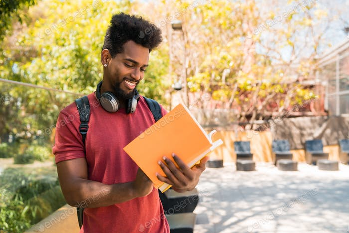 Afro university student studying and reading his book.