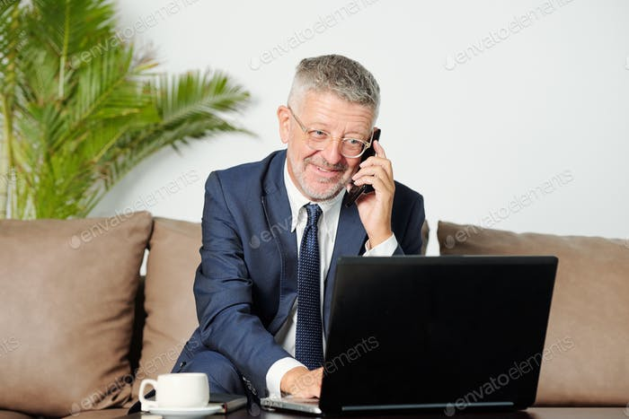 Smiling senior businessman talking on phone