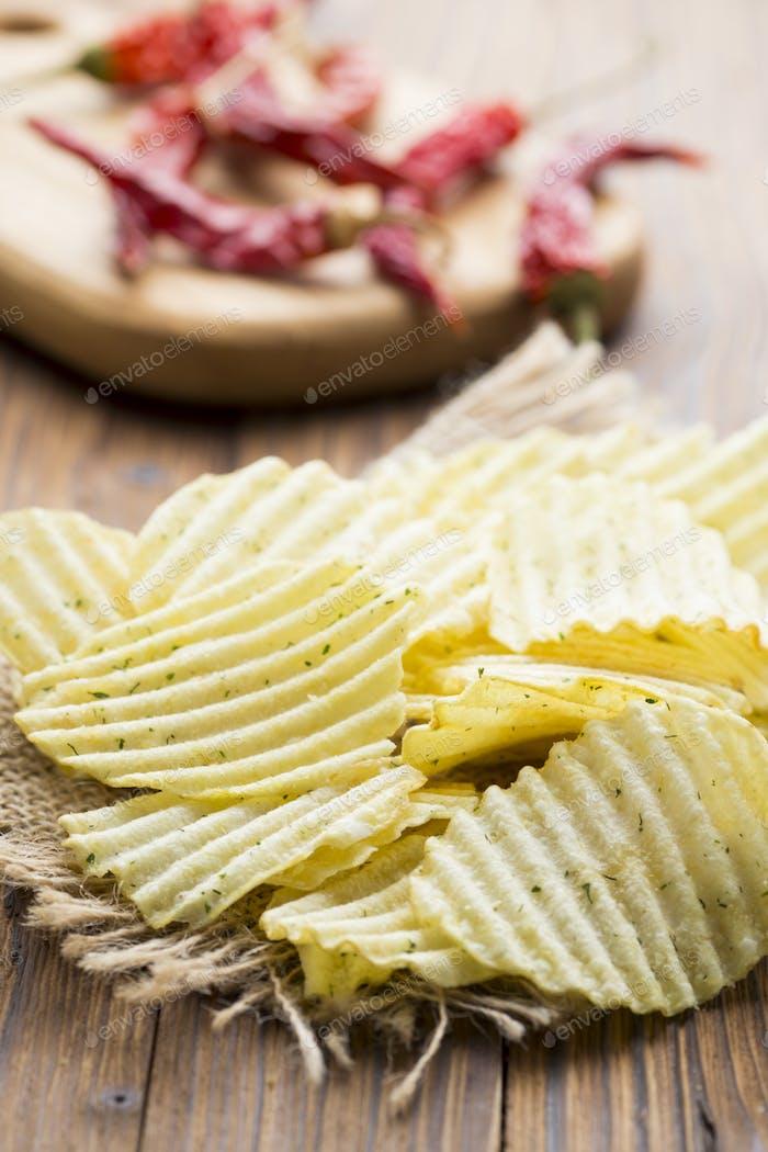 Eco potato chips on a wooden background. Studio photo.