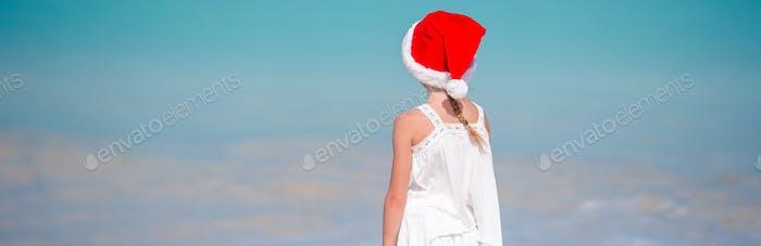 Adorable little girl in Santa hat on tropical beach
