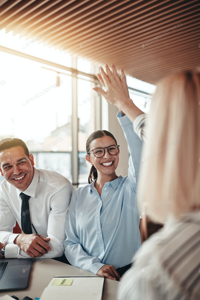 Laughing businesswomen high fiving together in an office