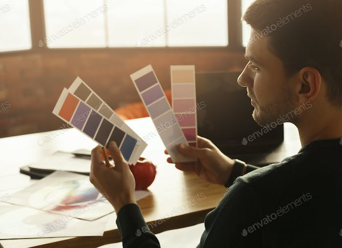 Guy Working With Color Samples Sitting At Laptop In Office