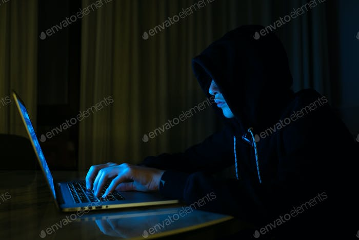 Junge in einem dunklen Raum mit Laptop. Hacker mit einem Laptop.