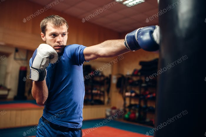 Male kickboxer hits the punching bag in gym