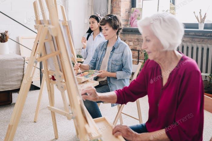 Artists Painting in Row in Art Studio